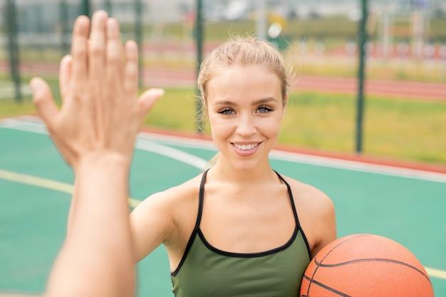 Mooie jonge blonde vrouw in activewear high-five geven aan haar vriend voor een spelletje basketbal op speelplaats