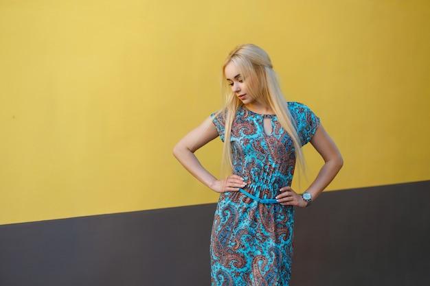 Mooie jonge blonde vrouw in blauwe jurk met een patroon in de buurt van de gele muur op een zomerdag