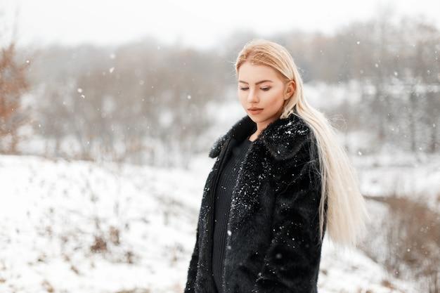 Mooie jonge blonde vrouw in bontjas poseren in winter park
