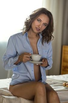 Mooie jonge blonde vrouw in de slaapkamer op het bed in lingerie en shirt met kopje koffie