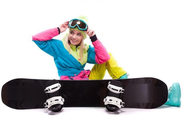 Mooie jonge blonde vrouw in kleurrijke sneeuw pak met gekruiste benen zit