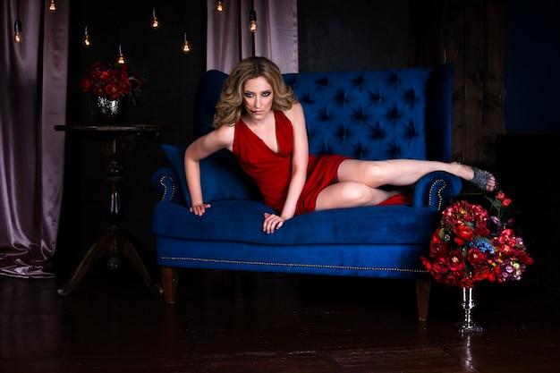 Mooie jonge blonde vrouw in rode jurk met halloween-make-up en bloedige gezichtskunst, vintage interieur