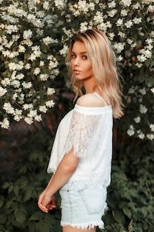 Mooie jonge blonde vrouw in vintage wit kanten t-shirt met denim shorts in de buurt van bloemen