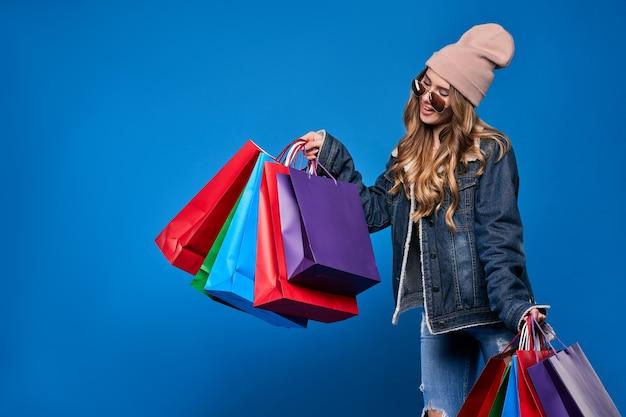 Mooie jonge blonde vrouw in zonnebril, jas en een hoed met pakketten in de uitverkoop