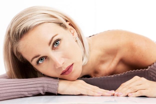 Mooie jonge blonde vrouw ligt op tafel. detailopname. witte achtergrond.