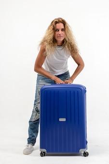 Mooie jonge blonde vrouw met blauwe plastic koffer op witte muur