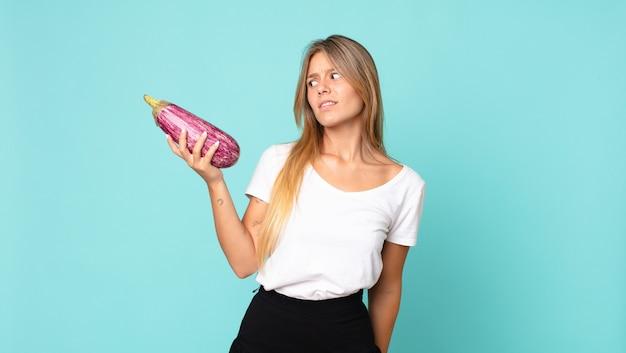 Mooie jonge blonde vrouw met een aubergine