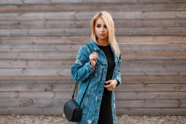 Mooie jonge blonde vrouw met een stijlvolle lederen handtas in een modieuze spijkerjasje in een zwarte jurk in de buurt van een vintage houten muur