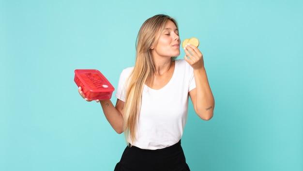 Mooie jonge blonde vrouw met een tupperware