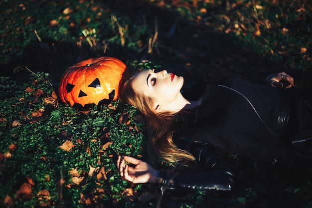 Mooie jonge blonde vrouw met extravagante make-up in een zwart lederen jas met wijd open ogen en een open mond met een pompoen in handen