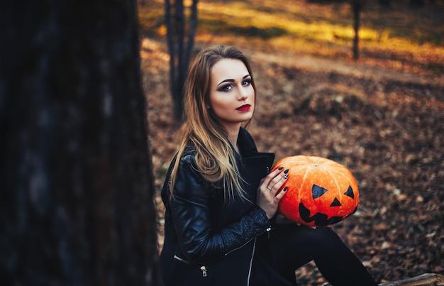 Mooie jonge blonde vrouw met extravagante make-up in een zwart lederen jas
