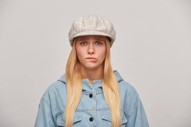 Mooie jonge blonde vrouw met lang haar naar beneden, beledigd, boos, beet op haar onderlip