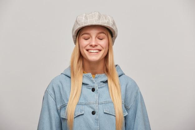 Mooie jonge blonde vrouw met lang haar naar beneden, ziet er gelukkig uit alsof ze droomt van iets aangenaams en inspirerend