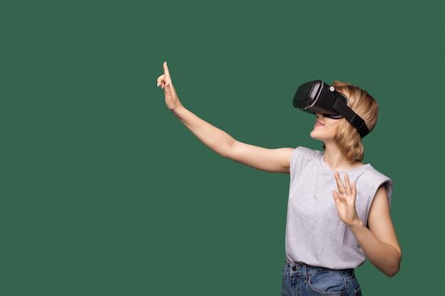 Mooie jonge blonde vrouw met vr-headset die iets op de groene vrije ruimte aanraakt