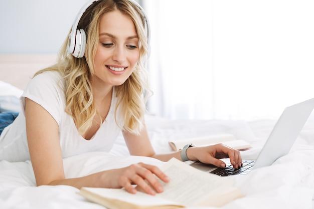 Mooie jonge blonde vrouw ontspannen in bed thuis, luisteren naar muziek met koptelefoon, studeren met laptopcomputer en schoolboeken