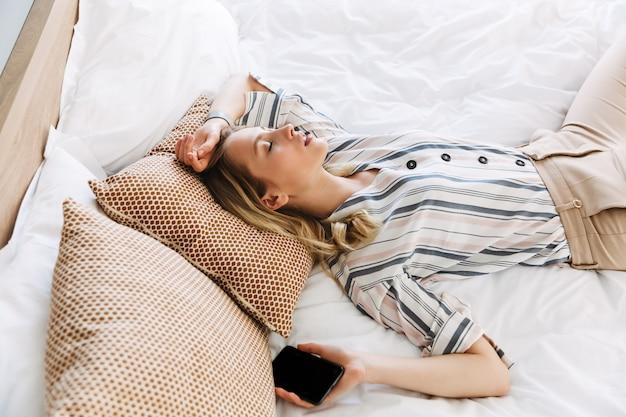 Mooie jonge blonde vrouw ontspannen in bed thuis, slapen met een leeg scherm mobiele telefoon