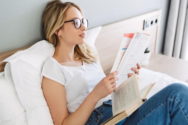 Mooie jonge blonde vrouw ontspannen in bed thuis