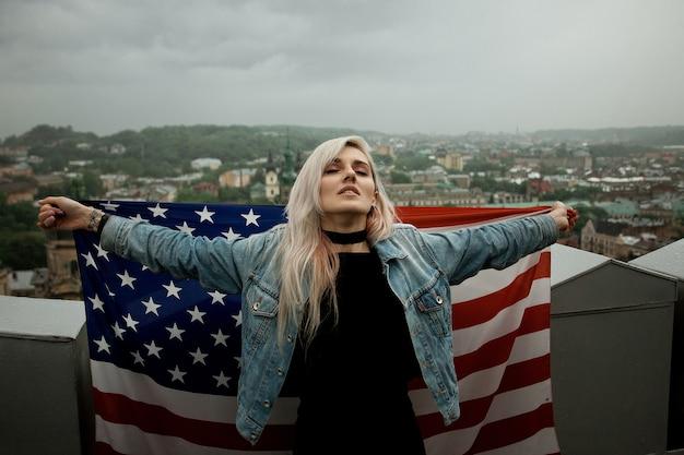 Mooie jonge blonde vrouw op een stadsruimte met amerikaanse vlag