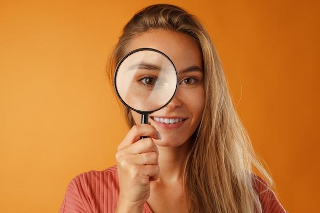 Mooie jonge blonde vrouw op zoek naar jou door vergrootglas close-up
