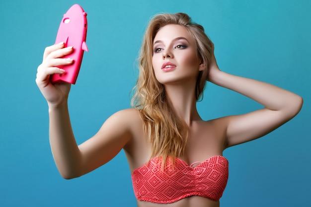 Mooie jonge blonde vrouw poseren in zwembroek en met telefoon
