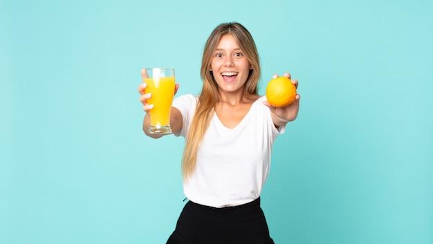 Mooie jonge blonde vrouw sinaasappelsap concept