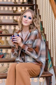 Mooie jonge blonde vrouw zittend op de trap van carrousel en koffie drinken in park