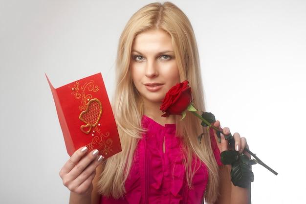 Mooie jonge blonde vrouwen met rode roos