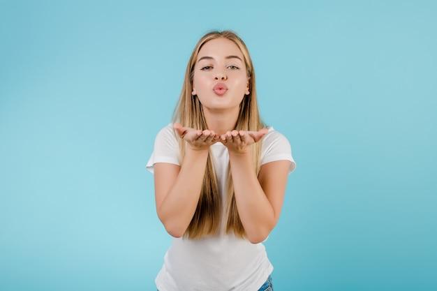 Mooie jonge blondevrouw die smooch kus verzendt die over blauw wordt geïsoleerd