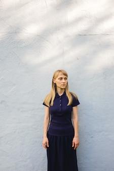 Mooie jonge blondevrouw in blauw polooverhemd die bij witte steenmuur zich in openlucht bevinden