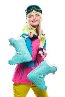 Mooie jonge blondevrouw in kleurrijke de sneeuwlaarzen van de sneeuwlaag