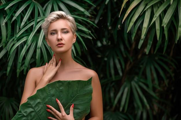 Mooie jonge blondevrouw met perfecte huid en lange lichtblonde haarvoorzijde van installatie tropische groene bladeren