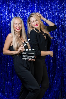 Mooie jonge blondines met make-up en een kapsel in een strak figuur van zwarte kleren hebben plezier en plezier op een feestje op een blauw glanzende fotozone