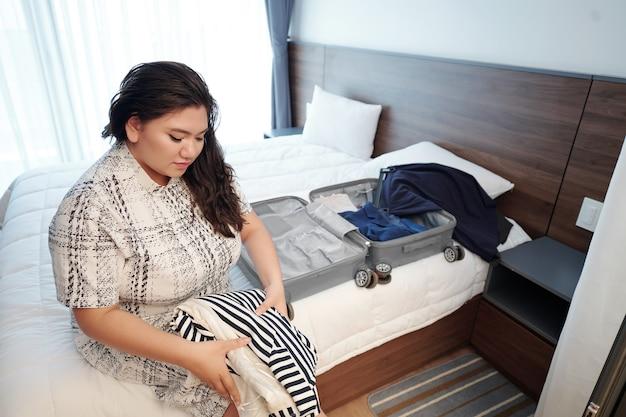 Mooie jonge bochtige vrouw zittend op bed en kleding in koffer inpakken en hotelkamer verlaten