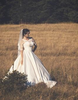Mooie jonge bruid buiten in een bos.