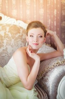 Mooie jonge bruid die op een luxueuze bank ligt.