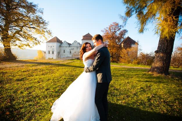 Mooie jonge bruid en knappe bruidegom die in openlucht dichtbij oud herenhuis bij zonsondergang dansen
