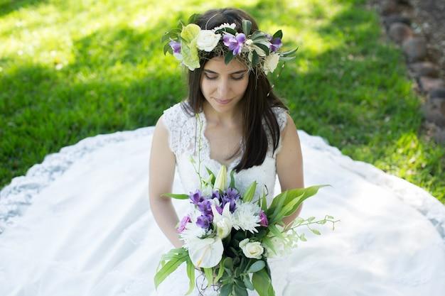 Mooie jonge bruid in een krans met een boeket in de hand