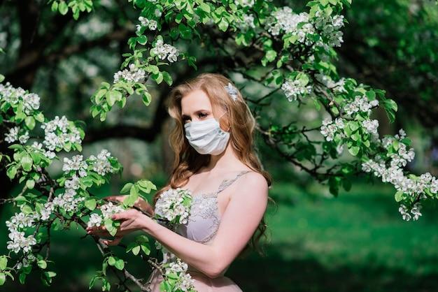 Mooie jonge bruid in een trouwjurk en een wit medisch masker op haar gezicht in de buurt van een bloeiende appel.