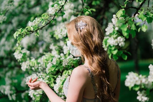 Mooie jonge bruid in een trouwjurk en een wit medisch masker op haar gezicht in de buurt van een bloeiende magnolia. covid-19 beschermt.