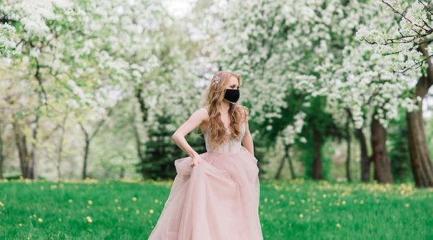 Mooie jonge bruid in een trouwjurk en een zwarte medische masker op haar gezicht in de buurt van een bloeiende appelbomen. covid19-bescherming.