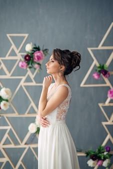 Mooie jonge bruid in een trouwjurk kijkt uit het raam met grijze muur en roze bloemen