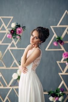 Mooie jonge bruid in een trouwjurk met grijze muren en bloemen op de achtergrond