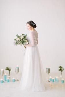 Mooie jonge bruid in een witte jurk met een boeket bloemen poseren in een hal met witte muren en versierde vloer met bloemen en kaarsen