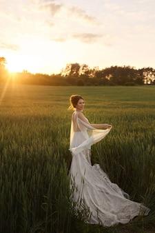 Mooie jonge bruid in kant trouwjurk op het veld op de zonsondergang