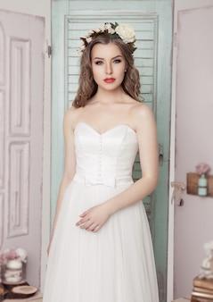 Mooie jonge bruid in roze en groene huwelijks romantische decoratie. houten kistenflessen en verschillende huwelijksdecoratie