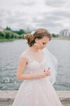 Mooie jonge bruid in witte de holdingsbloem van de huwelijkskleding bij aard.