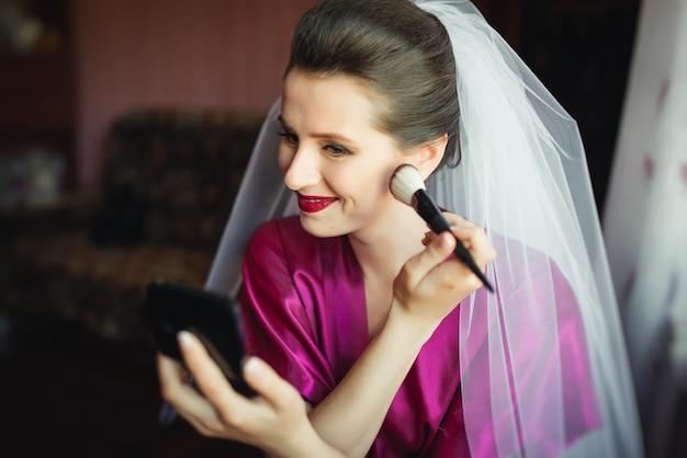 Mooie jonge bruid met bruiloft make-up en kapsel in de slaapkamer