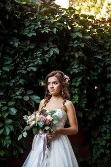 Mooie jonge bruid met een boeket van huwelijksbloemen.