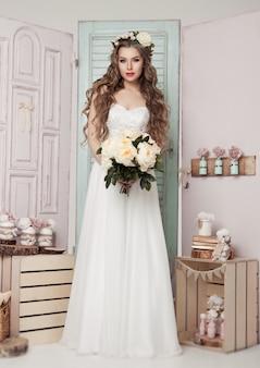 Mooie jonge bruid met kroonbloemen en romantische roze en groene decoratie. houten kistenflessen en verschillende huwelijksdecoratie
