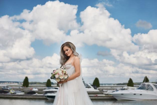 Mooie jonge bruid met platina blond haar in kant trouwjurk houdt boeket verse bloemen en poseren aan de kust van het meer.